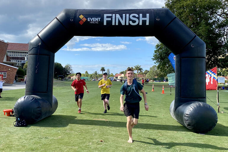 Dilworth Anglican School students cross the finish line during their run for the House to House fundraising event.