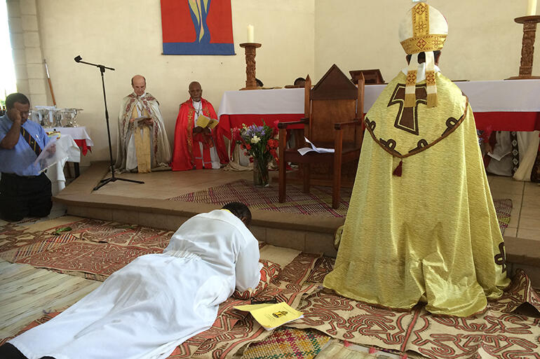 Bishop-to-be Denny Bray Guka prostrates himself before the altar at St Martin's Church, East Boroko.