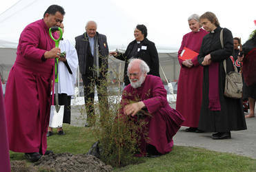 Archbishop Rowan plants a kowhai on the site where Waipounamu will erect a new church and community centre.