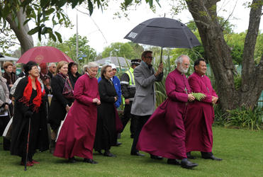 The Archbishop and his team advance towards the paepae. Bishop Kito Pikaahu guided him every step of the way.