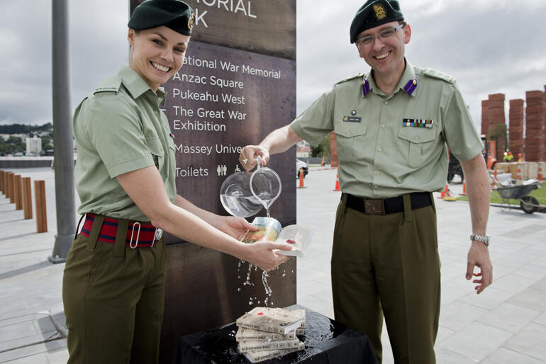 Second Lieutenant Claire Debrois and NZDF Chaplain Lance Lukin test the waterproof New Testaments at Pukeahu National War Memorial Park, Wellington.
