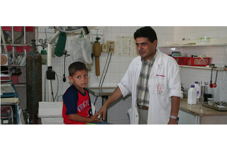A doctor at Al Ahli Hospital treats a young Gazan resident.
