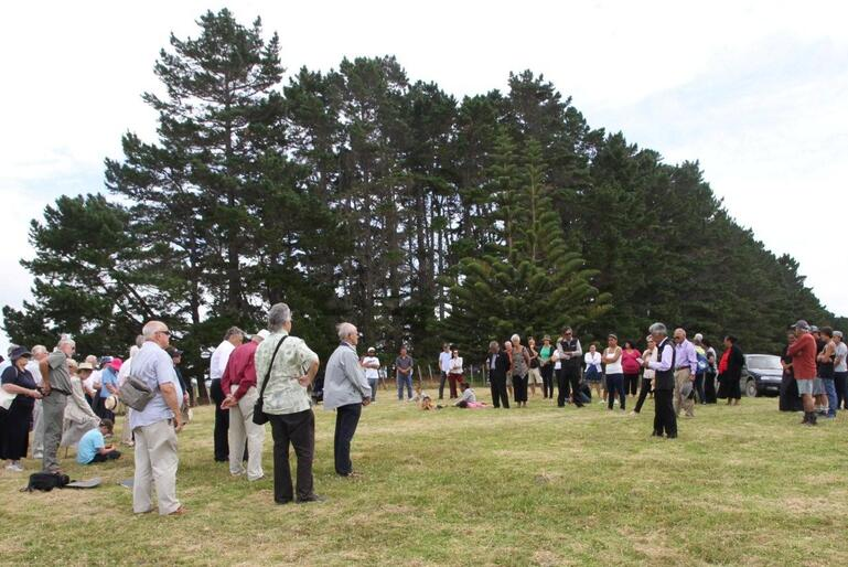 Hugh Rihari speaks during the powhiri. Folk are standing the site where The Interpretive Centre will be built.
