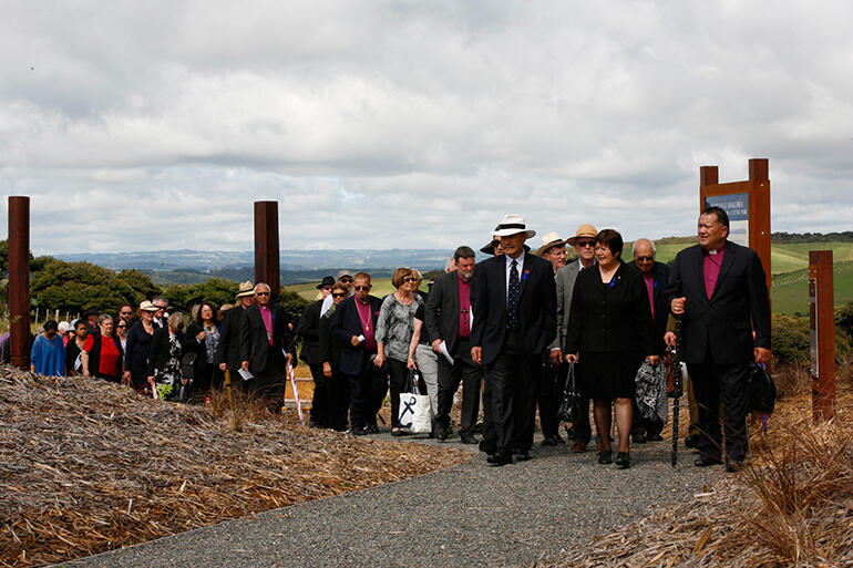 As the clouds begin to burn off, Bishop Kito Pikaahu leads the Governor General and manuhiri to the powhiri.