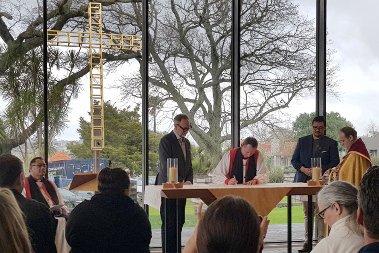 Bishop Ross Bay signs alongside Museum CEO David Gaimster (L) and Te Ariki Tamaroa Whatumoana (R), backed by Bishop Te Kitohi Pikaahu.