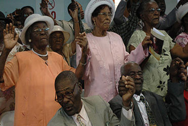 Jamaicans at the ACC's opening Eucharist join hands to sing a call-and-response version of the Lord's Prayer.