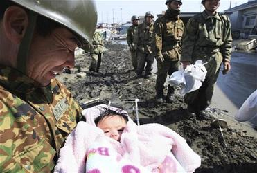A rescuer weeps for joy as he cradles a 4-month-old child found alive after three days in a ruined house in northern Japan. Photo: AP