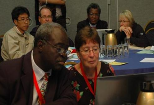 Abraham Yisa (Nigeria) and the Rev Janet Trisk (Southern Africa) follow the debate during an ACC plenary meeting in Kingston.