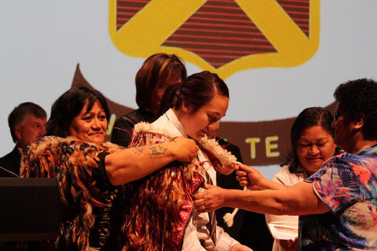The Dux, Raiha Falcon-Maxwell, has the korowai placed on her by the principal, Lelie Pearcey, and  Hukarere Board chair, Evelyn Taumaunu.