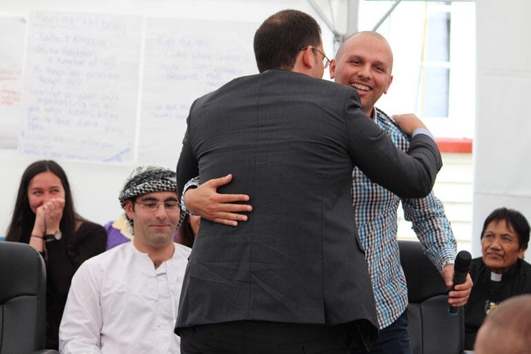 David Cumin, a Jew, and Tamer Elhardy, a Muslim, embrace during the discussion on Israel and Palestine.