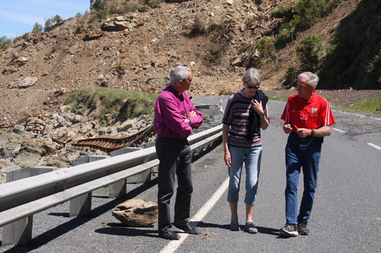 Bishop Richard and Hilary walk near the northernmost slip on State Highway One, as Malcolm explains the road closure's impact on farmers.