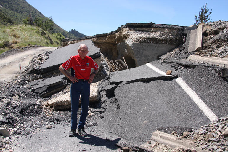 Malcolm Taylor stands on a formerly flat section of road, which was thrust up by over a metre in the Nov 14 earthquake.