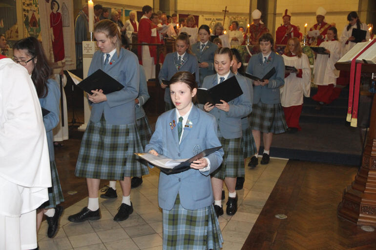 Singers from St Hilda's Collegiate process out before their new bishop.