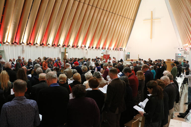 Synod members stand to sing during this year's Synod Eucharist at the Christchurch Transitional Cathedral.