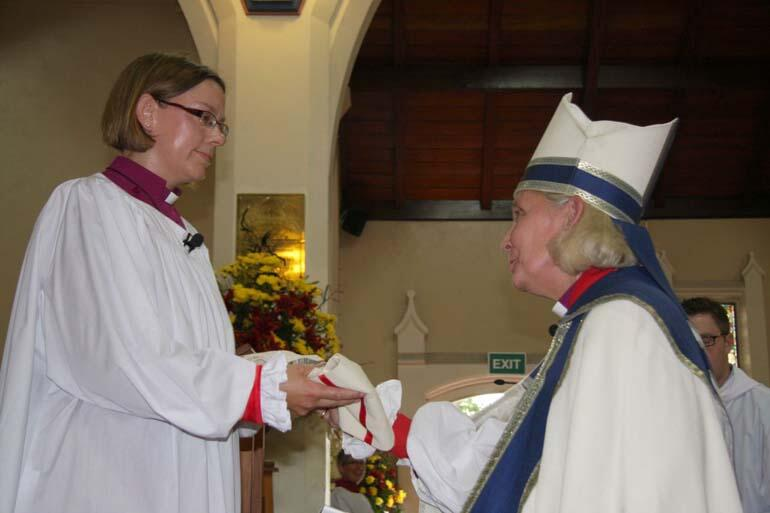 On behalf of the gathered bishops, Bishop Victoria Matthews presents Bishop Helen-Ann with her chole.