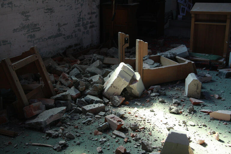 Rubble and upended prayer kneelers near the organ loft at Holy Trinity Avonside.