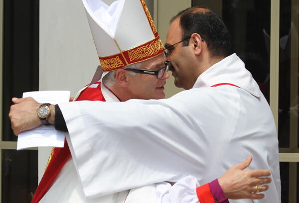 Rev George Al-Kopti embraces the new bishop. Fr George is a Palestinian priest studying for his doctorate at St John's College.