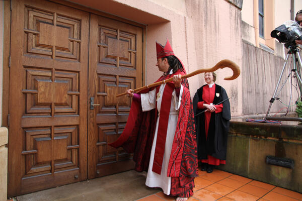 The new bishop strikes The Canterbury Door three times before being led inside to his new cathedra.