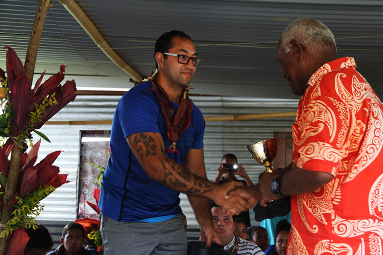 Isaac Beach presents Mosese Kakaramu, the koro headman, with a communion set.