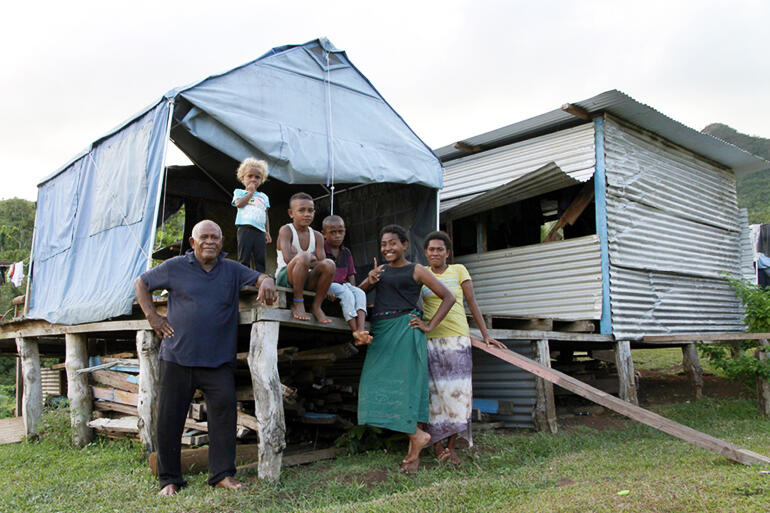That's Mosese Kakaramu at left, with his family, and the tent they live in these days. Mosese was the village chief.
