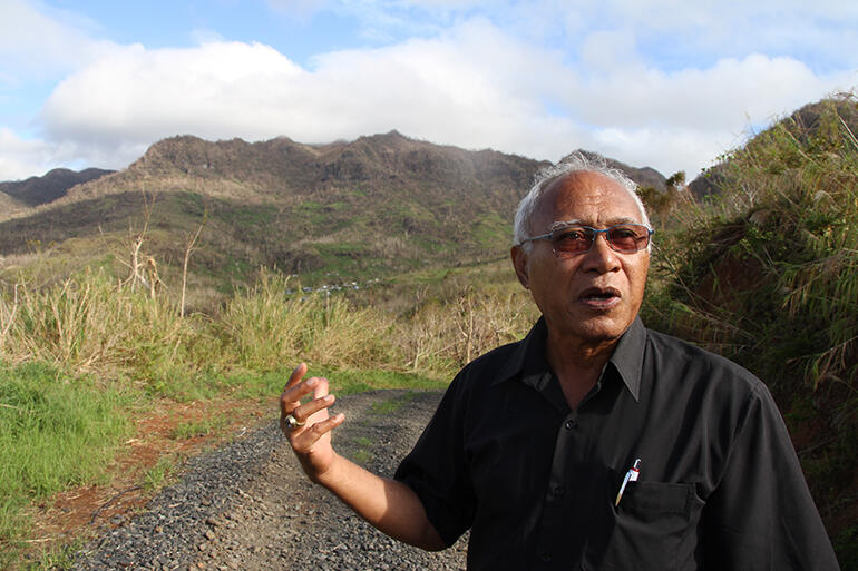 Archbishop Winston Halapua stopped on the road into Maniava to explain the history of the settlement - which can just be seen above his hand.