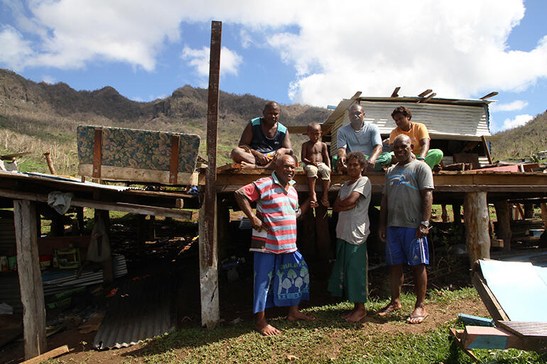 Mosese Kakaramu (in the striped jersey) stands in front of his basement, where his family rode out the cyclone which destroyed his two storey house.