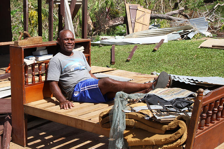 Waisake Raikadroka finds reason to keep smiling: his bed survived the Maniava maelstrom more or less intact.