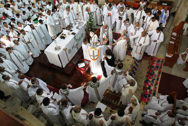 The priests of the diocese form an unbroken chain around a newly consecrated priest.