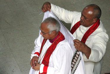 Archdeacobn Tui Finau of Tonga drapes the cope over Bishop Winston's shoulders.