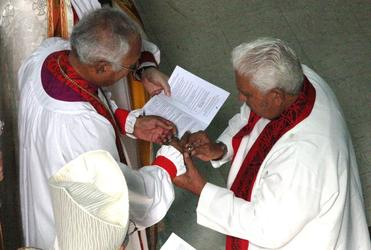 Archdeacon Schwalger places the episcopal ring on Bishop Winston's finger.