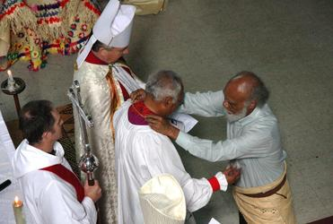 Dr Sitiveni Halapua drapes the pectoral cross around his brother's neck.