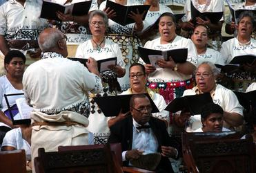 Fr Tomu has a spell while the choir from the Ofa ki he Laumalie Ma'oni'oni, the Tongan Anglican church in Otahuhu, takes a turn.