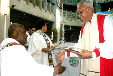 Archbishop Winston congratulates Fr Demesi, one of the clergy who went through the non-violence workshops.