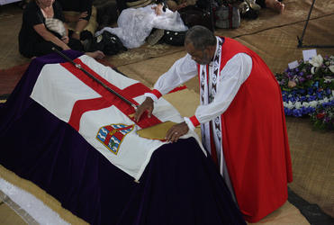 Bishop Api Qiliho lays the Archbishop's mitre and crozier on the casket.
