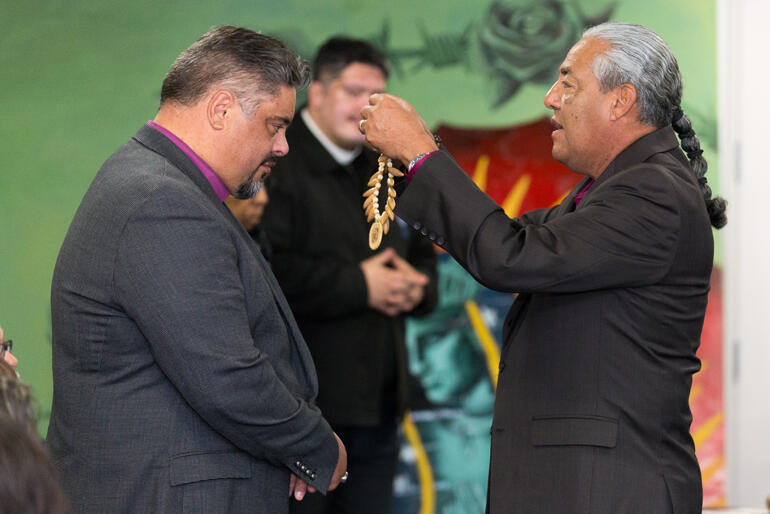 Indigenous church leader Canon Andy Orozco offers a gift of recognition to Archbishop Don.