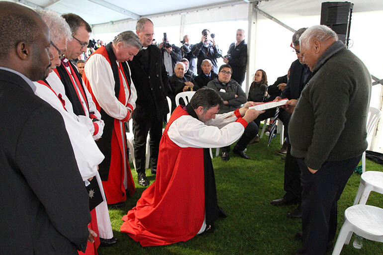 Archbishop Philip, on bended knee, offers the church's apology to kaumatua of the Otamataha Trust, which represents Ngati Tapu and Ngai Tamarawaho.