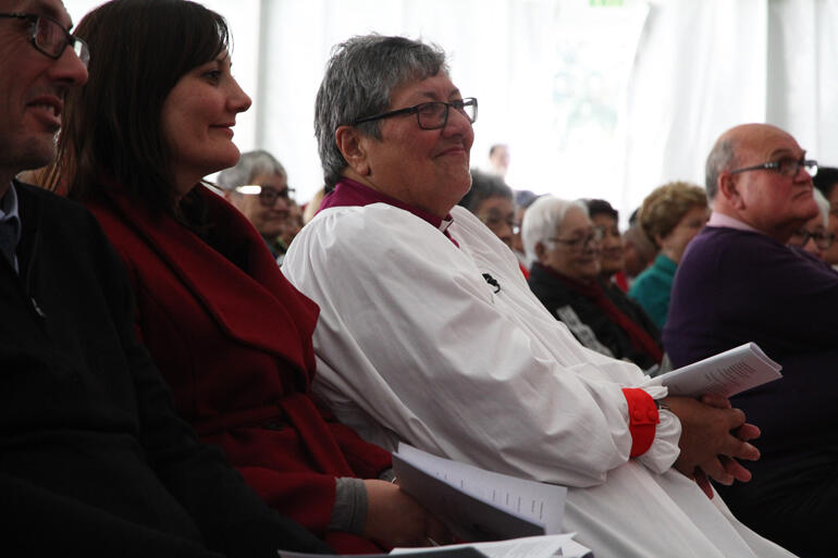Bishop Waitohiariki smiles in response to Dr Jenny Te Paa Daniel's words, as she sits flanked by whanau.
