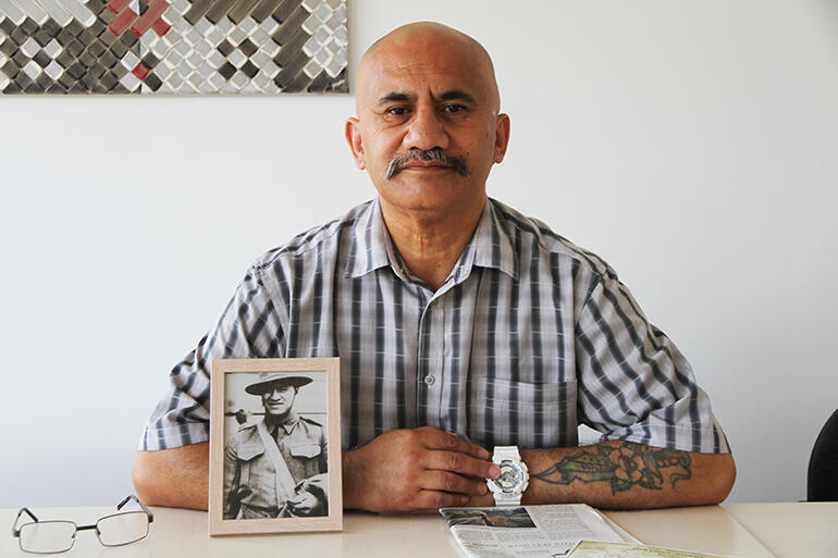 Colenso Eramiha, who is Kaiwhakamana at the John Kinder Theological Library in Auckland, with a portrait of his Uncle Sonny at his elbow.