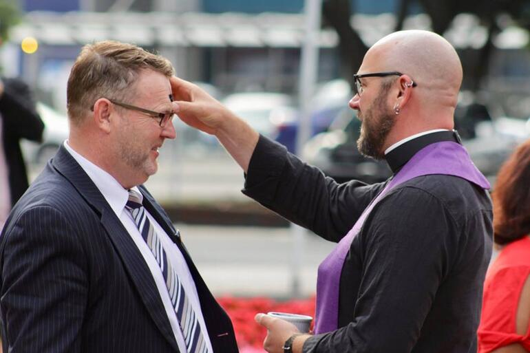 Rev Joe McGarry imposes ashes on one of the dozens who took up the offer of ashes to go today.