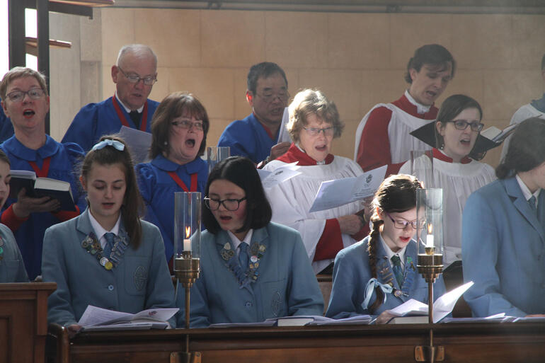 Members of St Hilda's, St Paul's Cathedral and St John's Roslyn choirs join in song.