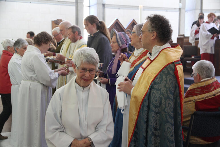 Rev Cushla McMillan smiles after receiving the Eucharist and anointing during the 150th festival service.