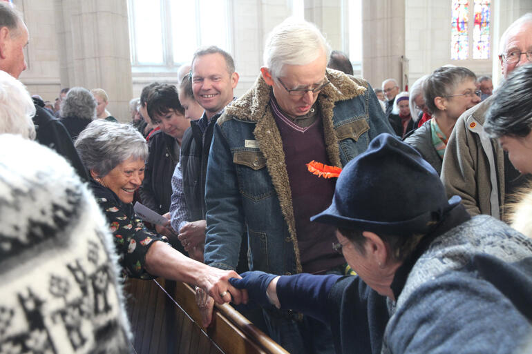 Worshippers pass the peace at St Paul's Cathedral Dunedin on Sunday 15 September.