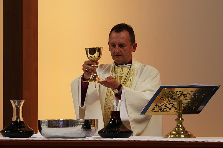 Bishop Ross Bay elevates the chalice during The Great Thanksgiving.