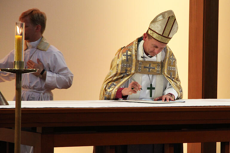 Bishop Ross Bay signs the Consecration Charter on the high altar.