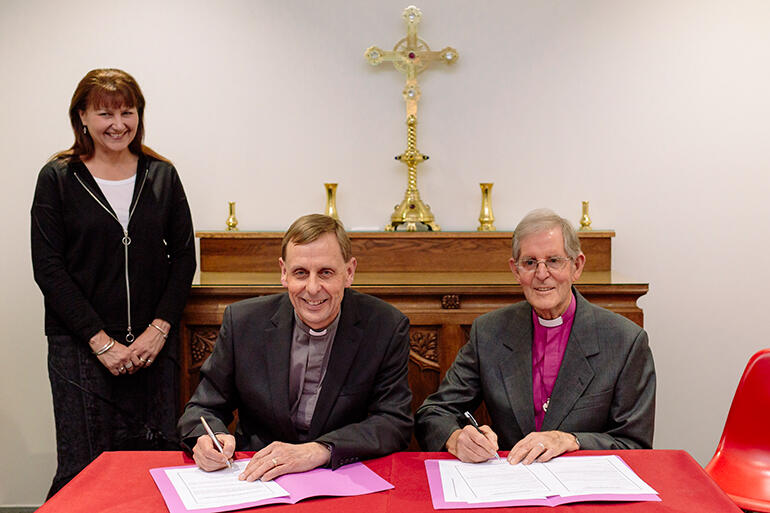 The bishop-elect signs up before two witnesses - his dad, Bishop Brian Carrell, and his wife, Teresa Kundycki-Carrell.