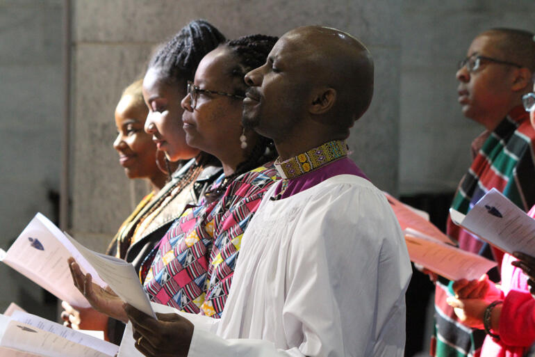 Steve Maina worships God as he approaches his new calling supported by his wife Watiri Maina and daughters Tanielle and Rinna.