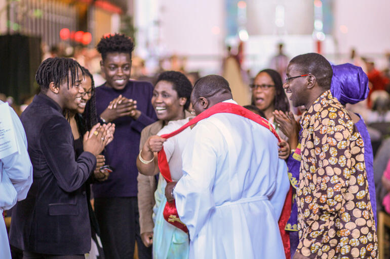 Rev Froduald Mugiraneza from Journey Christian Fellowship at St Paul's Waiwhetu shares a light moment with supporters as he joins the diaconate.