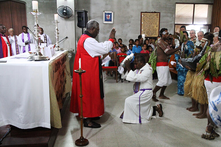 Archbishop George Takeli of Melanesia blesses the Bible, which is about to be read by Fr Harry Gereniu.