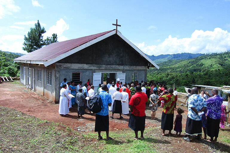 Archbishop Winston speaks to the villagers before they file into the church for the first service.