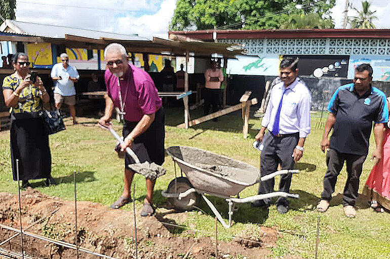 Bishop Henry Bull smiles for the camera as he wields a spadeful of cement headed for a classroom foundation at St Mary's Anglican School in Labasa.